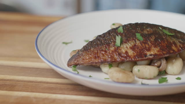pan fried sea bass fillet with chestnut mushroom gnocchi - sea bass stock videos & royalty-free footage