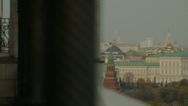 Pan from a balcony onto a wide shot of the Kremlin on a grey day in Moscow, Russia.
