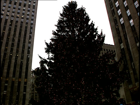 pan from a huge christmas tree to holiday ice skaters enjoying the rockefeller center skating rink in new york. - rockefeller center christmas tree stock videos & royalty-free footage