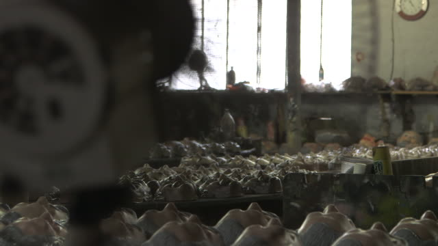 Pan from a standing fan to rows of plastic masks laid out on tables in a factory.