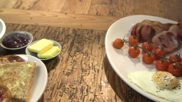 stockvideo's en b-roll-footage met pan from a traditional cooked english breakfast to cornflakes, toast and jam, uk. - table top shot