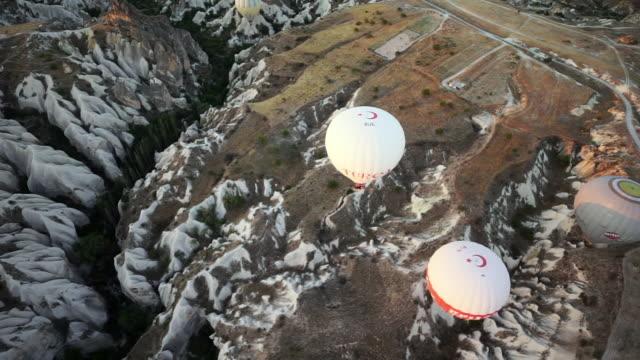 pan from above of hot air balloons over turkish white rocks - cappadocia, turkey - three objects点の映像素材/bロール