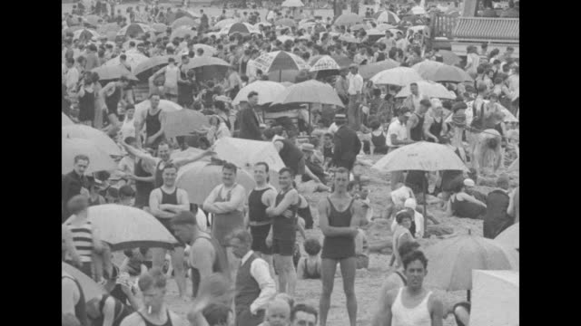 """pan from building marked """"cafeteria"""" across crowded beach filled with men, women & children and many beach umbrellas / vs a few police and some... - swimwear stock videos & royalty-free footage"""