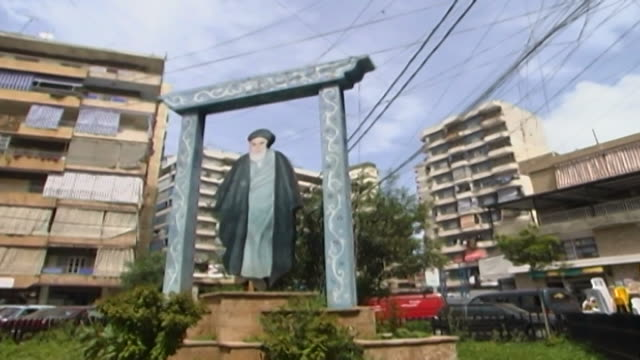 pan from buildings to a garden in a residential area in dahieh district a framed cutout of grand ayatollah ruhollah khomeini the late 1st supreme... - shi'ite islam stock videos & royalty-free footage