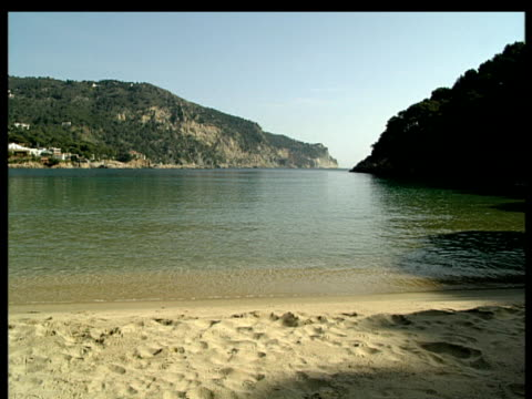 pan from calm inlet to empty sand beach surrounded by low rocky cliff. costa brava spain. - inlet stock videos & royalty-free footage