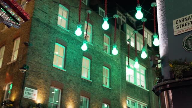 vídeos de stock, filmes e b-roll de pan from carnaby street sign to glittering carnaby union jack at night - vanguardista