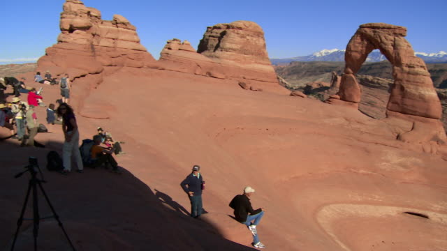Pan from crowd of people to Delicate Arch