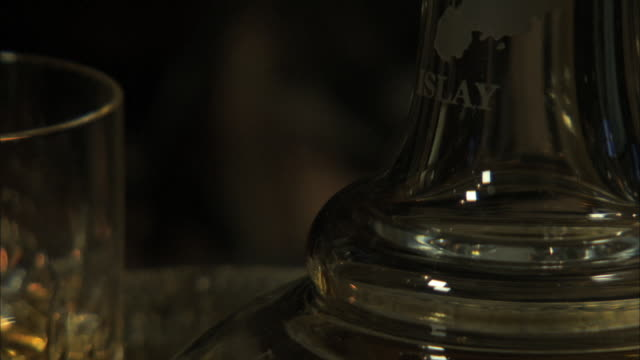 """cu pan from decanter to glasses of scotch malt whisky with fireside lighting. """"islay"""" engraved on the decanter - decanter stock videos & royalty-free footage"""