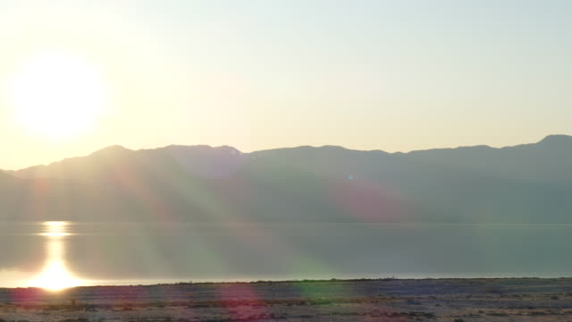 4k pan from golden sun rays reflecting off water to pestel grey mountains on the horizon shorebirds in the lake - faglia di sant'andrea video stock e b–roll