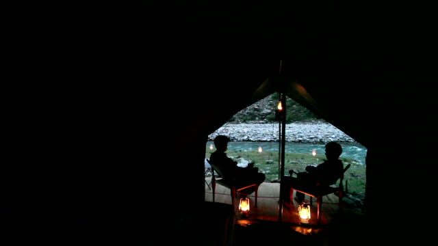 Pan POV from inside safari style tent of two men toasting with drinks and two beds with lanterns and river in background.