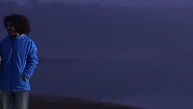 stockvideo's en b-roll-footage met ms pan from lake to group of young people standing by side of lake at dusk drinking and chatting - duurzaam toerisme