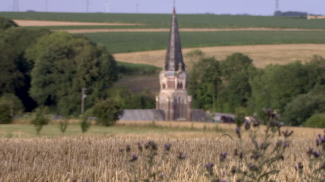 vídeos de stock e filmes b-roll de pan from lavender to a church sitting below fields in an area heavily affected by wwi, northern france. - spire