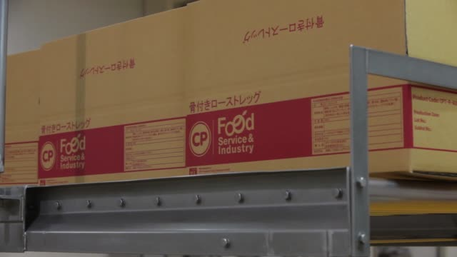 Pan from left to right of cardboard boxes lined up above the packaging section Zoom into CP logo displayed on a cardboard box An employee drives a...