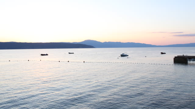 pan from left to right over a bay on the island krk in croatia at sunset, a boy is fishing off the jetty. - mare adriatico video stock e b–roll
