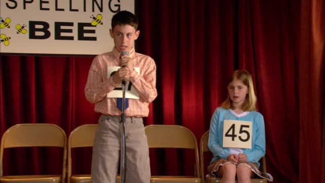 Pan from moderator of spelling bee announcing word to boy walking up to microphone to spell word / pan in to boy struggling to spell word / pan to other finalist on stage back to boy relieved to spell word correctly / Los Angeles, California