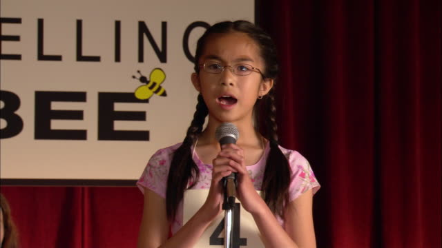Pan from moderator of spelling bee announcing word to girl walking up to microphone and spelling word / pan to other competitors sitting on stage / girl sitting down / Los Angeles, California
