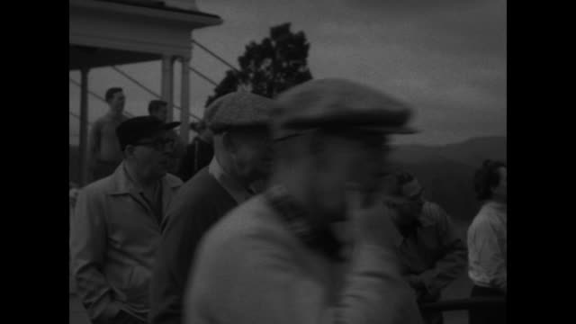 pan from news photographers crouched on grass to president dwight d eisenhower under umbrella / quick shot of news photographers / profile of ike... - golf swing from behind stock videos & royalty-free footage