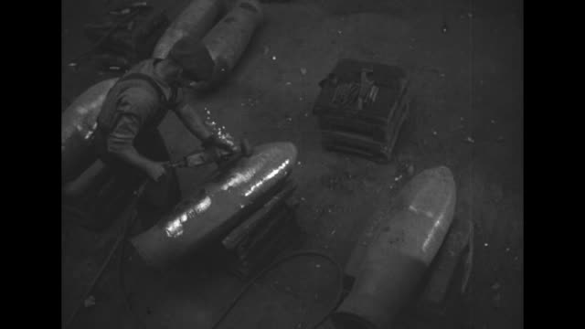 vidéos et rushes de pan from overhead men use grindingsanding tool on bombs / cu bombs standing / pan to men smoothing out interior of bomb / ms men adjusting and... - armement