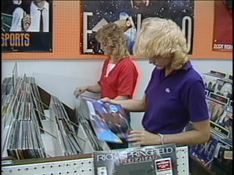 pan from poster on wall to md two young women shopping for records - rock stock-videos und b-roll-filmmaterial