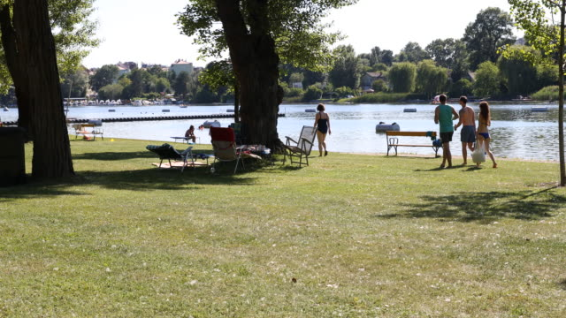 Pan from right to left across the lawn at the famous public beach called Gänsehäufel on the shore of the Alte Donau in Vienna in Austria