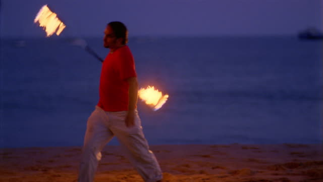 pan from right to left of man twirling flaming stick and woman twirling flaming chains on beach at dusk / california - 棒切れ点の映像素材/bロール