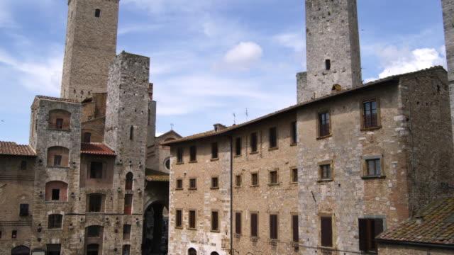 pan from sky to piazza della cisterna wide angle - periodo medievale video stock e b–roll