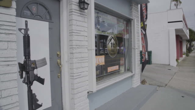 stockvideo's en b-roll-footage met pan from street to gun shop storefront in melbourne - vuurwapenwinkel