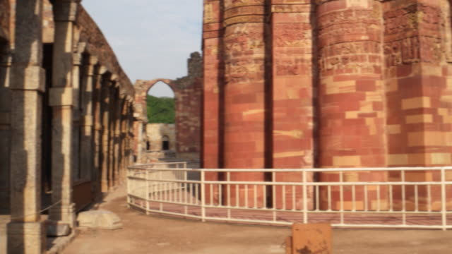 a pan from the entrance arch of alai darwaza to the majestic qutb minar, delhi - minareto video stock e b–roll