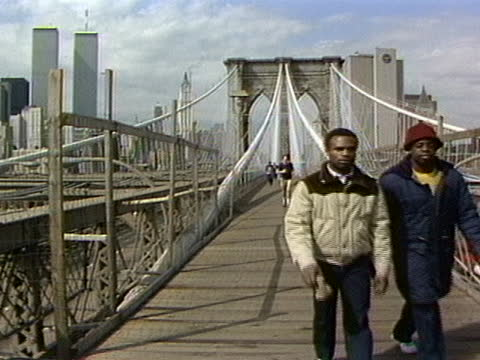 pan from the statue of liberty to the brooklyn bridge with runners and joggers in the 1980s. - brooklyn bridge stock videos & royalty-free footage