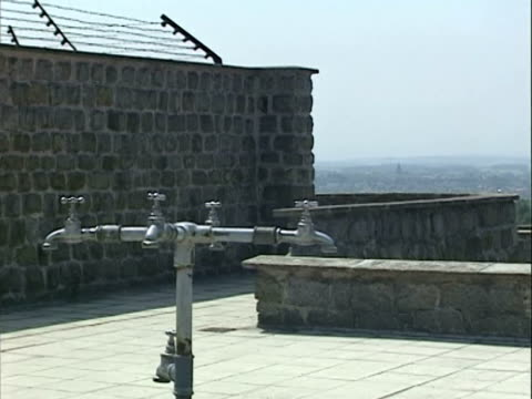 / pan from top of the stone walls of the camp with surrounding countryside in view / CU water faucets