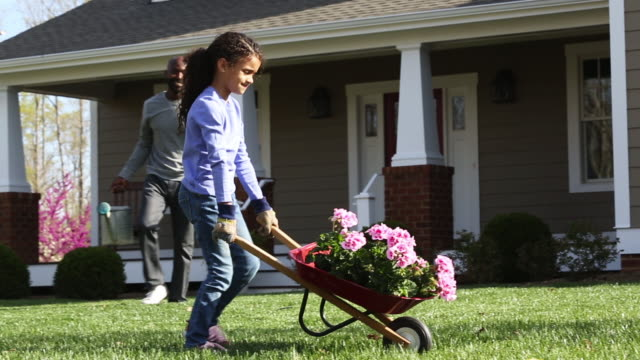 ws pan girl pushes wheelbarrow of flowers in yard/ richmond, virginia usa - wheelbarrow stock videos and b-roll footage