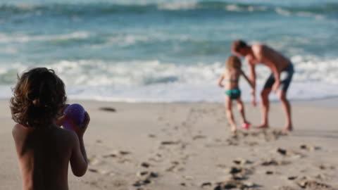 ms r/f pan girl throws water balloon at man, boy carries water balloon over and also throws at man on beach / montezuma, puntarenas, costa rica - kelly mason videos stock videos & royalty-free footage