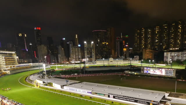 tl pan hong kong happy valley horse race course at night - spoonfilm stock-videos und b-roll-filmmaterial