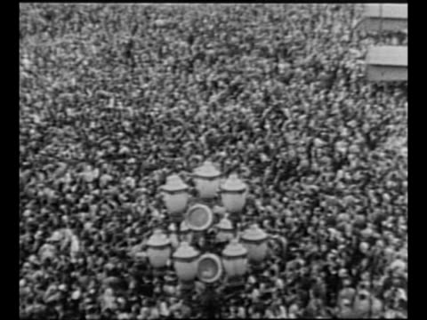 pan huge crowds in plaza de mayo in buenos aires / montage priest conducts religious meeting in streets as people chant, hold rosaries / elderly... - priest stock videos & royalty-free footage
