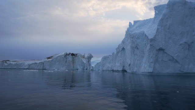 pan: huge icebergs floating in disko bay against sky - inlet stock videos & royalty-free footage