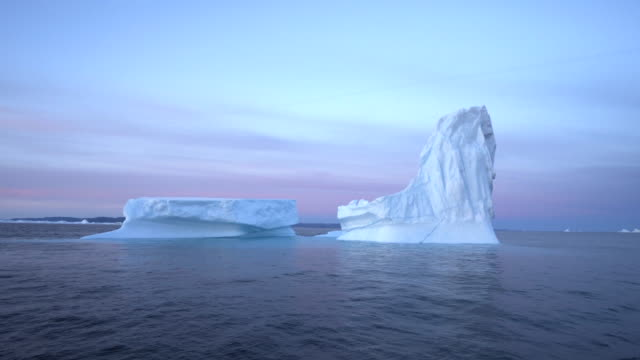 pan: huge icebergs of different forms in the disco bay - disko bay, greenland - bay of water stock-videos und b-roll-filmmaterial