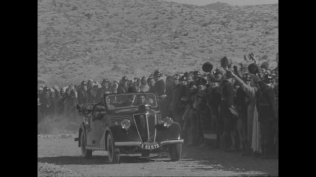 pan hundreds of civilians in western clothes stand in desert watching southern tunisia army troops parade through sand / french premier and war... - ceremonial robe stock videos and b-roll footage