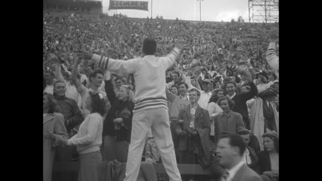 ws pan int los angeles memorial coliseum with packed stands and teams entering field arches and clock tower stand in background / loudspeakers stand... - pom pom stock videos & royalty-free footage