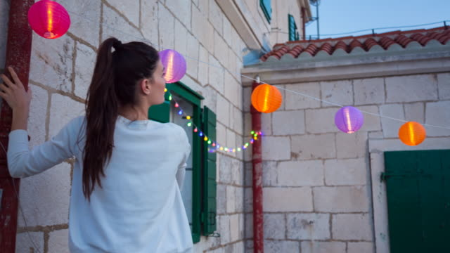 vídeos de stock e filmes b-roll de cu pan l woman hanging up lanterns for outdoor party - preparação