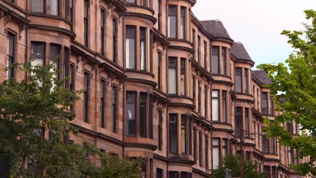 pan: large sandstone tenements with enormous windows above lush green trees - glasgow, scotland - ジョージア調点の映像素材/bロール