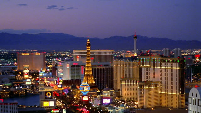 Pan Las Vegas Strip past Eiffel Tower and Chrysler Building replicas with MGM Grand at dusk