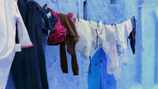 pan: laundry hanging on clothes line - washing line stock videos and b-roll footage