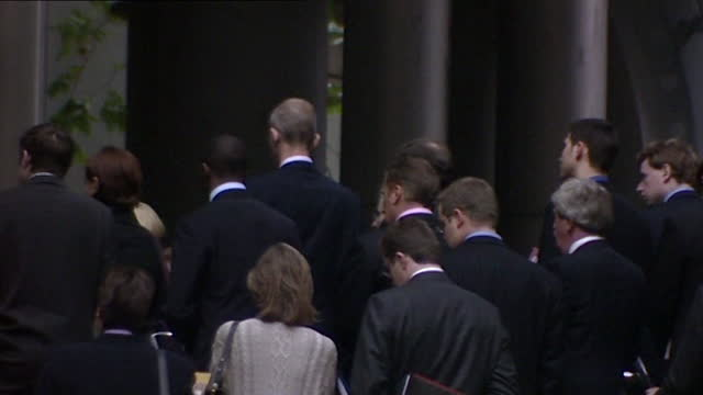 pan left across a large group of city workers in london standing on the doorstep of an office building as they hold a minute's silence to honour the... - only men stock videos & royalty-free footage