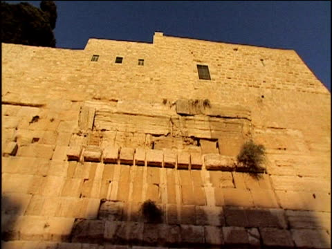 pan left across ancient stone wall against blue sky temple mount jerusalem - gerusalemme est video stock e b–roll