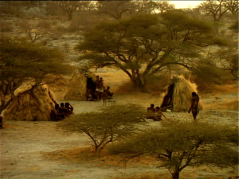pan left across basarwa village. - ボツワナ点の映像素材/bロール