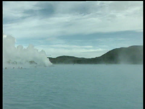 Pan left across billowing steam to bathers in turquoise geothermal springs steam rises up out of water Blue Lagoon Iceland