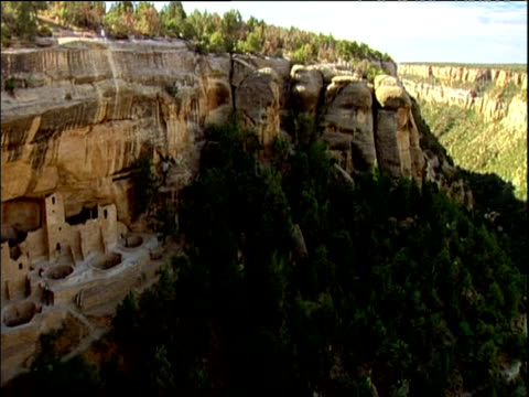 pan left across canyon to mesa verde cliff dwelling ruins national park colorado - mesa verde nationalpark stock-videos und b-roll-filmmaterial