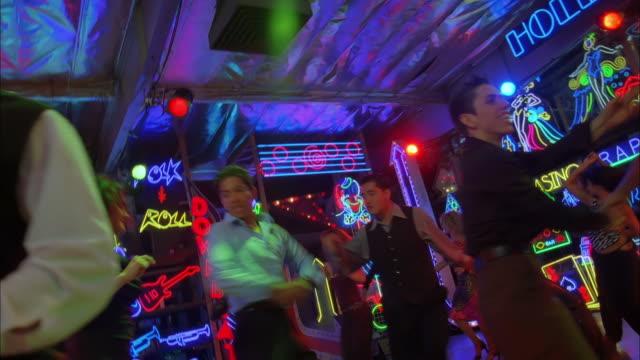 pan left across dance floor and tilt up to couples salsa dancing in nightclub, los angeles available in hd. - ペア点の映像素材/bロール