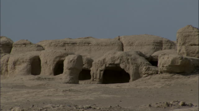 Pan left across eroded arches and walls of Jiaohe, Xinjiang province, China,
