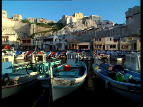 Pan left across fishing boats moored in harbour with old town buildings stacked on hillside under clear blue sky Marseille